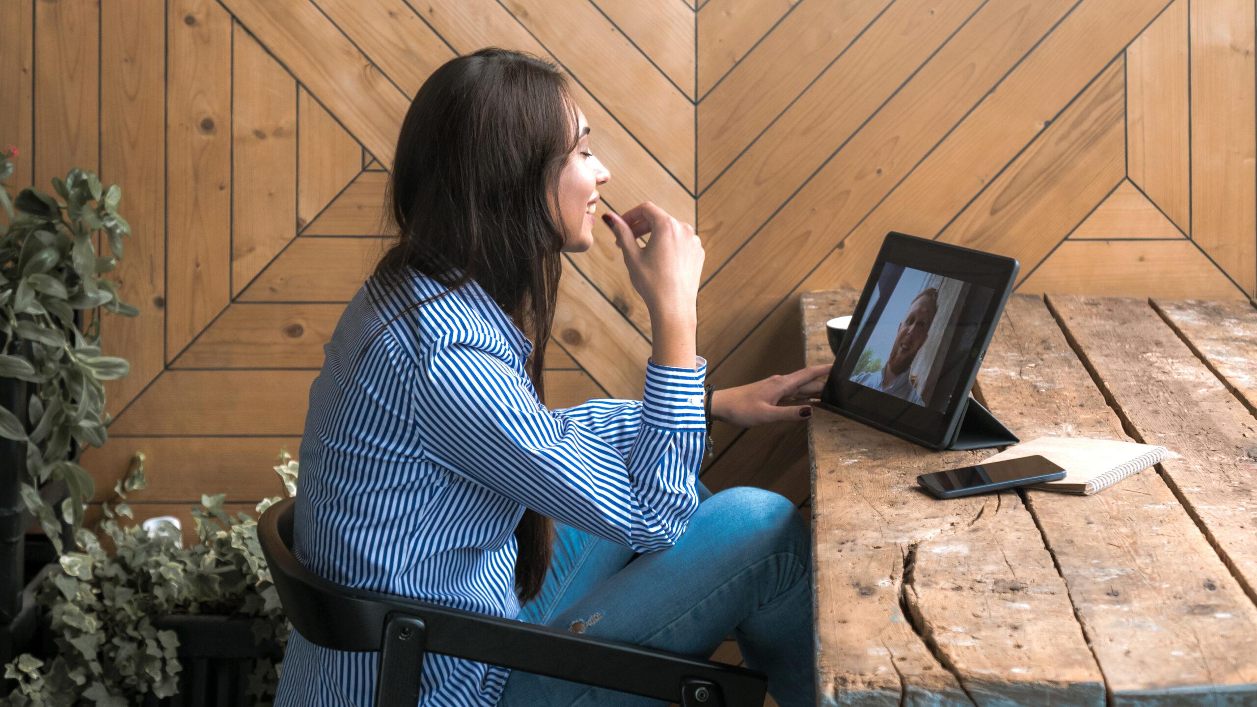 Frau mit Schwarzen Haaren, hat einen Videocall in einem Rustikalen Cafe